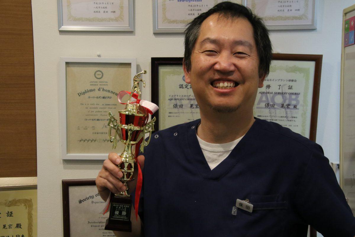 写真:卓球で獲得したトロフィーを手に笑顔の保田氏/撮影:ラリーズ編集部