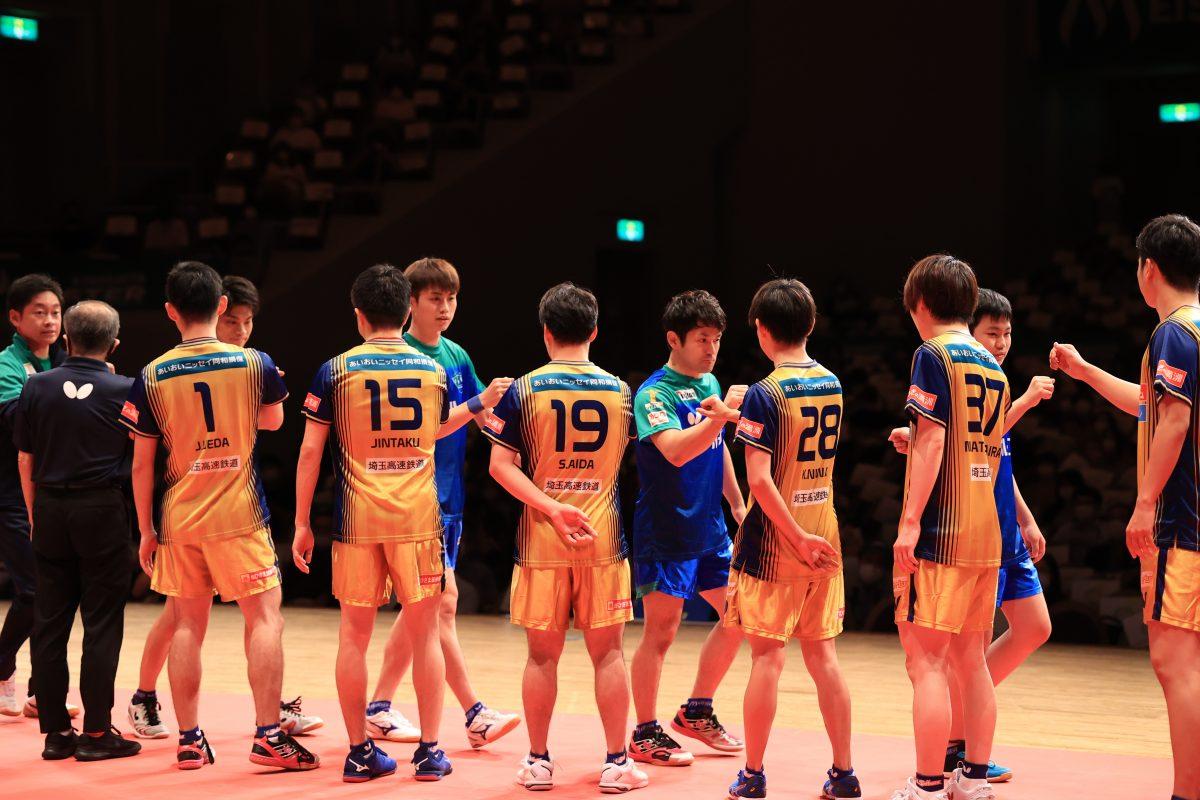 写真:試合前に肘タッチを交わす両チームの選手/撮影:槌谷昭人